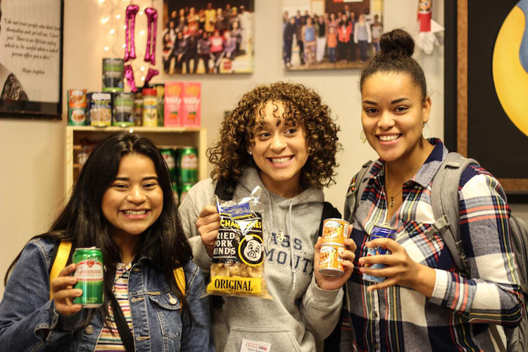 Three female students holding up food various food donations from the Daily Good